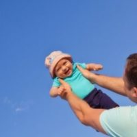 cute baby girl with hat being held up by her dad in a bright blue sky