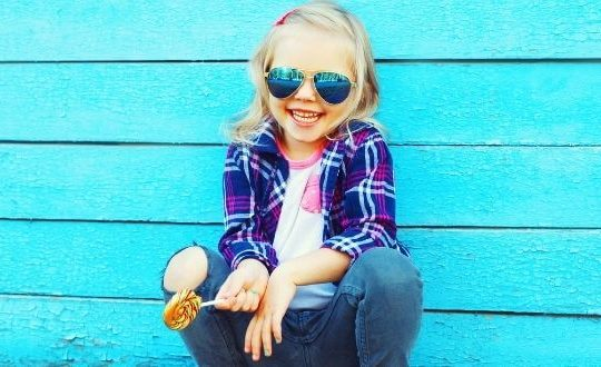 trendy little girl wearing sunglasses crouching in front of a bright blue wood wall