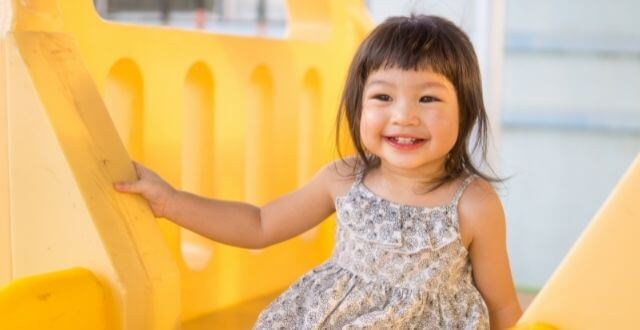 smiley toddler girl sitting on yellow play equipment