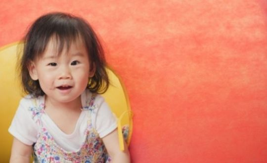 toddler girl in front of colorful slide