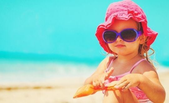 toddler girl at the beach in bright pink hat and sunglasses