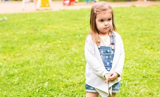 toddler girl standing on the grass looking uncertain