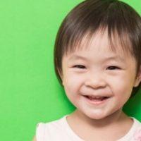 smiling toddler girl on green background