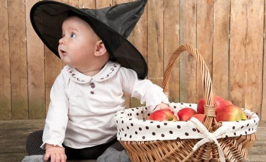 baby wearing a witch hat by a basket of apples